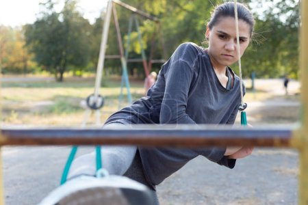 Photo for A young sportswoman on the nature playground does warm-up and stretching of the leg muscles Athletic woman stretching her leg at the park - Royalty Free Image