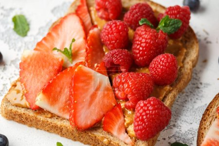 Photo for Peanut butter sandwiches with fresh strawberry, blueberry, raspberry and banana whole meal toasts - Royalty Free Image