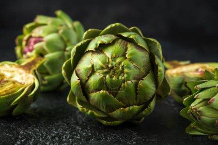 Photo pour Fresh raw organically grown artichoke flower buds on dark background. - image libre de droit