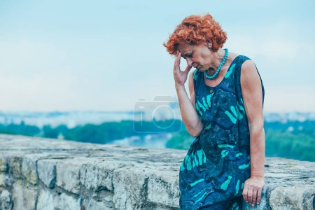 Depressed mature woman feeling alone outside
