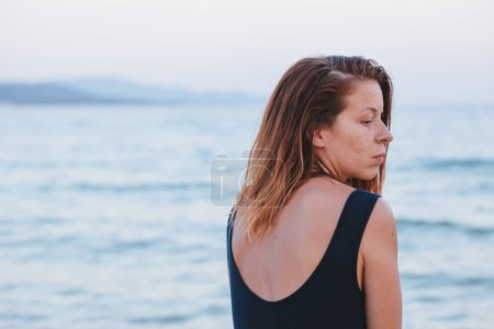 Photo for Woman alone and depressed sitting at the beach - Royalty Free Image