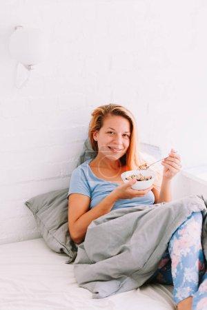 Photo pour Jeune femme petit déjeuner au lit - image libre de droit