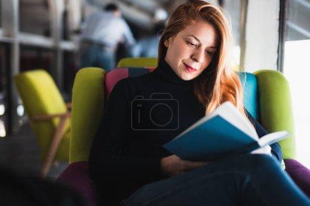 Photo pour Jeune femme assise dans un café lisant un livre - image libre de droit