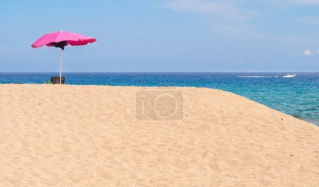 Pink parasol on sand overflow on a beach. Sea and blue sky in the background.
