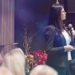 Beautiful business woman with microphone in her ha...