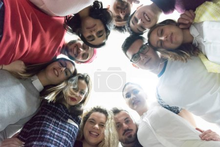 Photo for Bottom view of multiethnic group of volunteers looking down at camera isolated on white - Royalty Free Image