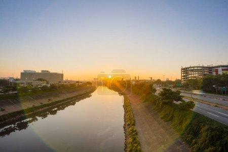 Salida del sol, inicio del día en metrópolis, luces brillantes y vehículos en tránsito. Autopista de la ciudad de Sao Paulo junto al río. Skyline, coches y tráfico en la carretera a alta velocidad .