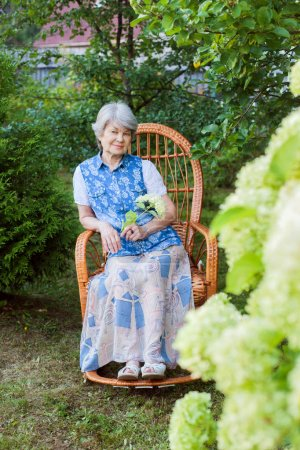 Photo for Pretty old woman resting in garden in rocking chair - Royalty Free Image
