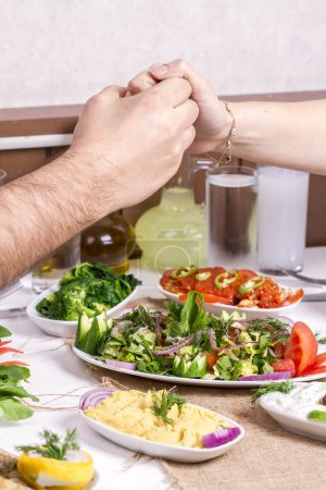 Photo for Couple holding by hands while having romantic dinner with different meals - Royalty Free Image