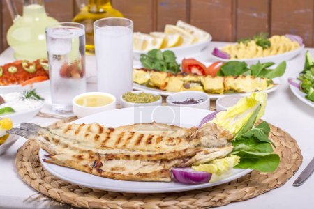 table setting with different grilled meals from meat, fish and vegetables