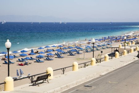 RHODES, GREECE - AUGUST 26, 2017: Akti Miaouli beach is located in short walking distance to Rhodes town and consists of grey pebbles and sand. It is not a particularly a wide beach, strip of sand.
