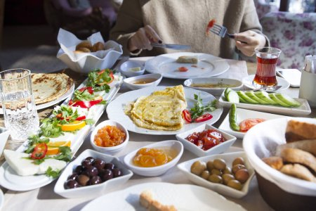 Photo pour Plan recadré de femme assise à la table servie avec divers plats - image libre de droit