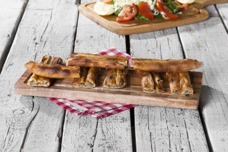 Photo for Close up view of freshly baked pastry and salad served on wooden table - Royalty Free Image