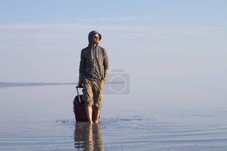 Photo pour Jeune homme avec des bagages marchant au bord de la mer seul - image libre de droit