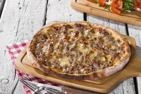 Photo for Close up view of cooked pizza and salad served on wooden background - Royalty Free Image