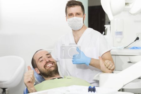 Photo pour Jeune dentiste et patient heureux à la clinique dentaire - image libre de droit