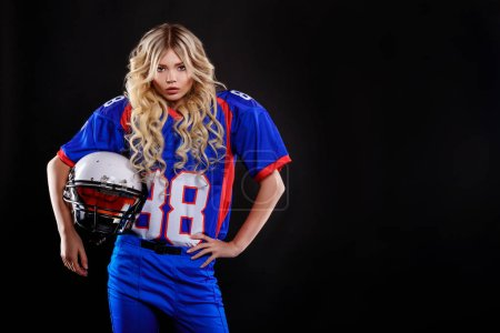 athletic blonde posing as american football player on black background. Beautiful young woman wearing American football top holding ball.