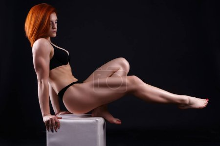 Young strong sexy woman showing her muscles in studio on black background