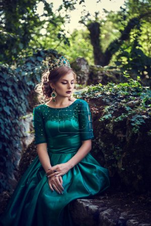 Photo pour Jeune femme vêtue d'une robe verte explore une forêt magique. L'idée et le concept de contes de fées, magie. - image libre de droit