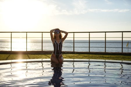 Photo for Woman Summer Fashion. Happy Sexy Smiling Girl With Fit Body, Long Legs, Healthy Skin In Bikini, Sunglasses Sunbathing By Swimming Pool On Travel Holidays Vacation. Beauty, Wellness, Lifestyle - Royalty Free Image