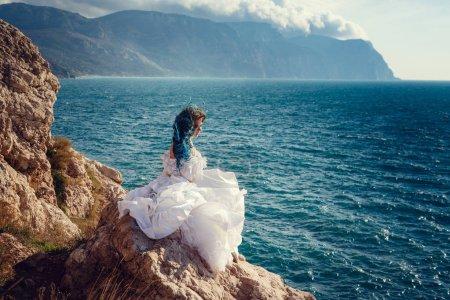 Photo pour Jeune femme debout sur le bord de la falaise et regardant dans une large vue sur la mer. Coiffure Wind Long Blue . - image libre de droit