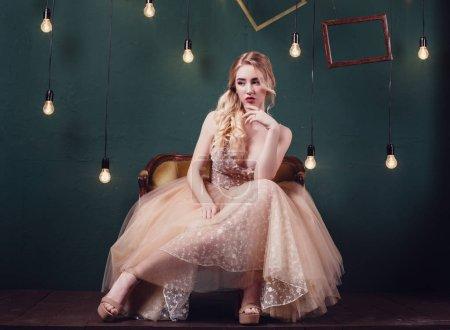 Photo pour Photo studio de mode de belle jeune fille aux cheveux bruns portant une robe beige luxueuse , - image libre de droit