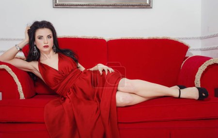 Photo for The beautiful girl in a long red dress posing in a vintage scene.Young beautiful woman wearing a red dress in the old hotel.Sensual elegant young woman in red dress and indoor shot. - Royalty Free Image