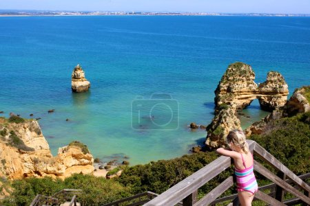 Wonderful view of Praia do Camilo in south of Portugal. Children taking scenic wooden path leading to one of the most spectacular places in Lagos, Algarve region.