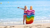 Happy little girl playing with colorful inflatable mattess in the sea or ocean. Child having fun on beautiful sandy beach. Cute kid enjoying summer vacation in hotel or resort. Luxury summer destination for family with children.