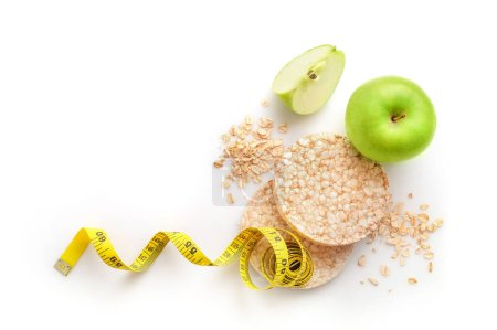 Photo for Rice diet bread, measure tape and apple isolated on white background. Diet concept. - Royalty Free Image