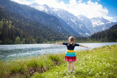 Photo for Child hiking in the Alps mountains looking at beautiful lake. Kid in alpine flower field at snow covered mountain in Austria. Spring family vacation. Little girl on scenic hike trail. Outdoor fun. - Royalty Free Image