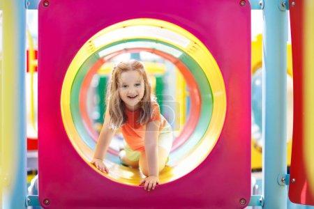 Photo pour Enfants grimpant et glissant sur une aire de jeux extérieure. Les enfants jouent dans le parc d'été ensoleillé. Centre d'activités et de loisirs dans la maternelle ou la cour de l'école. Enfant sur toboggan coloré. Enfant en bas âge en plein air . - image libre de droit