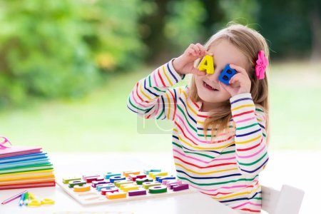 Photo for Child doing homework for school at white desk. Wooden educational abc toy puzzle for kids. Happy back to school student. Kid learning alphabet letters. Little girl with school supplies and books. - Royalty Free Image