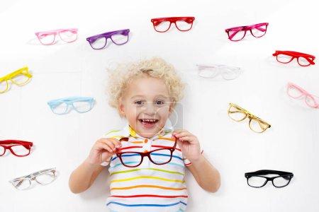 Test visuel enfant à ?il. Petit enfant qui choisit des lunettes dans un magasin d'opticiens. Mesure de la vue pour les écoliers. Vêtements oculaires pour enfants. Médecin qui vérifie les yeux. Bébé avec lunettes vue de dessus .