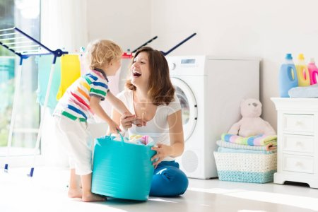 Photo for Mother and kids in laundry room with washing machine or tumble dryer. Family chores. Modern household devices and washing detergent in white sunny home. Clean washed clothes on drying rack. - Royalty Free Image