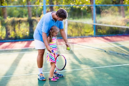 Photo for Father and daughter playing tennis on outdoor court. Family with tennis racket and ball at net in sport club. Coach teaching young kid. Child learning to play. Training for kids. Children exercise. - Royalty Free Image
