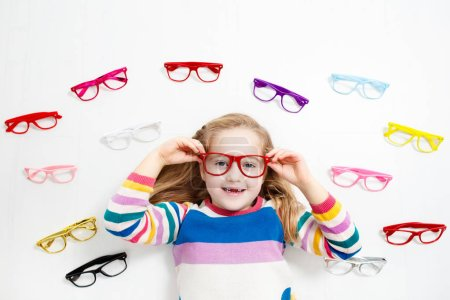 Child at eye sight test. Little kid selecting glasses at optician store. Eyesight measurement for school kids. Eye wear for children. Doctor performing eye check. Girl with spectacles at letter chart.