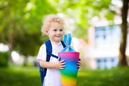 Photo pour Enfant heureux holding cône de bonbons allemand traditionnel le premier jour d'école. Peu d'étudiants avec sac à dos et livres heureux d'être de retour à l'école. Début de la classe en Allemagne avec des bonbons pour les enfants. - image libre de droit