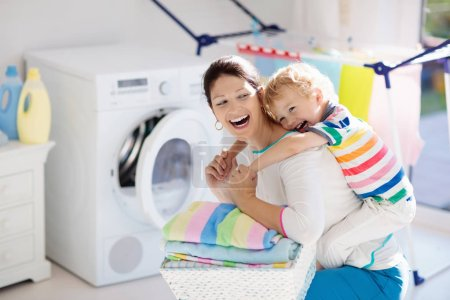 Madre e hijos en la sala de lavandería con lavadora o secadora. Tareas familiares. Dispositivos domésticos modernos y detergente de lavado en casa soleada blanca. Limpiar la ropa lavada en el estante .