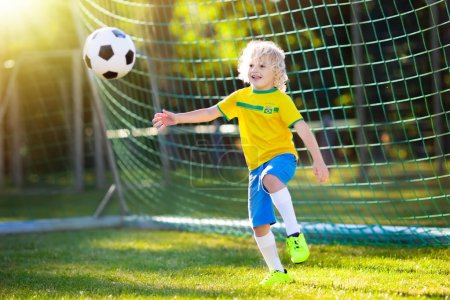Kids play football on outdoor field. Brazil team fans. Children score a goal at soccer game. Little boy in Brazilian jersey and cleats kicking ball. Football pitch. Sports training for player.