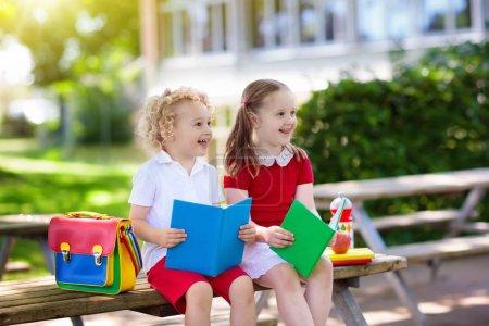 Photo pour Enfants retourner à l'école. Début de la nouvelle année scolaire après les vacances d'été. Garçon et fille avec sac à dos et de livres sur le premier jour d'école. Début de la classe. Éducation pour les enfants de maternelle et de préscolaire. - image libre de droit