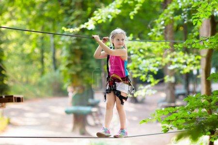 Foto de Niño en el parque de aventura forestal. Los niños suben por el sendero de cuerda alta. Agilidad y escalada centro de diversiones al aire libre para niños. Niña jugando al aire libre. Patio de la escuela patio con cuerda manera . - Imagen libre de derechos