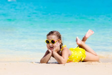 Child playing on tropical beach. Little girl at sea shore. Family summer vacation. Kids play with water and sand toys. Ocean and island fun. Travel with young children. Asia holiday.