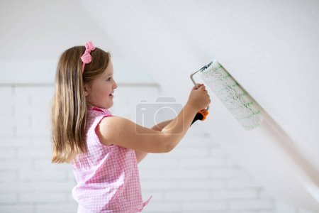 Kids painting attic wall. Home improvement and ren...