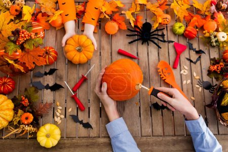 Family with child carving Halloween pumpkin and eating trick or treat candy on wooden table with autumn leaves decoration. Top view flat lay of kids hands, sweets and carved pumpkins.