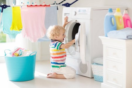 Niño en lavadero con lavadora o secadora. Un chico ayudando con las tareas familiares. Dispositivos domésticos modernos y detergente de lavado en casa soleada blanca. Limpiar la ropa lavada en el estante .