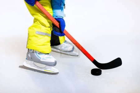 Child in skates playing ice hockey on indoor rink. Healthy winter sport for kids. Boy with hockey sticks hitting puck. Child skating. Little kid on sports training after school. Snow and ice fun.