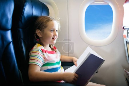 Photo for Child in airplane. Kid with book in air plane sitting in window seat. Flight entertainment for kids. Traveling with young children. Kids fly and travel. Family vacation. Girl reading book in airplane. - Royalty Free Image