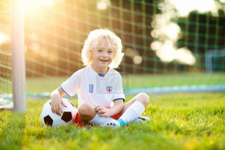 Photo for Kids play football on outdoor field. England team fans. Children score a goal at soccer game. Little boy in English jersey and cleats kicking ball. Football pitch. Sports training for player. - Royalty Free Image