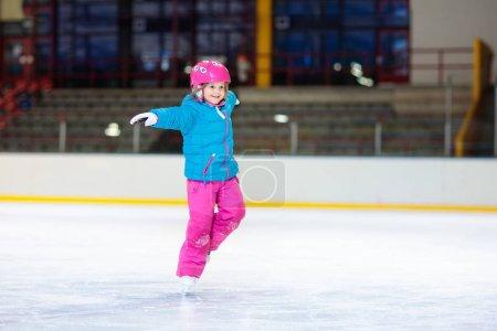 Photo pour Patinage pour enfants sur patinoire intérieure. Les enfants patinent. Sport familial actif pendant les vacances d'hiver et la saison froide. Petite fille en formation de vêtements colorés ou apprendre le patinage sur glace. Activité sportive et clubs scolaires - image libre de droit